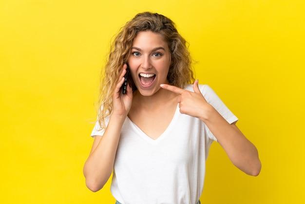 Giovane donna bionda che utilizza il telefono cellulare isolato su sfondo giallo che dà un gesto di pollice in alto