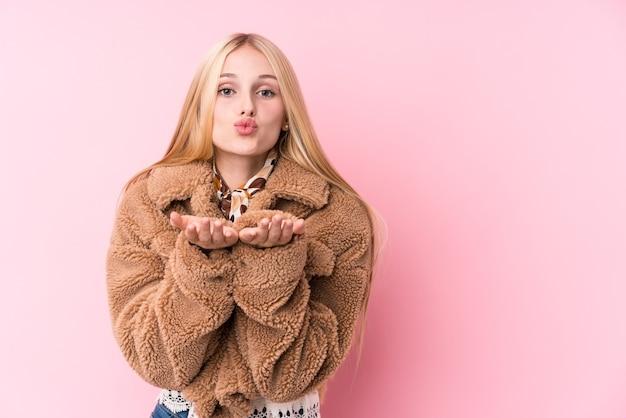 Giovane donna bionda che indossa un cappotto contro un muro rosa, piegando le labbra e tenendo le palme per inviare un bacio d'aria.