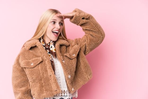 Giovane donna bionda che indossa un cappotto contro un muro rosa che guarda lontano tenendo la mano sulla fronte.