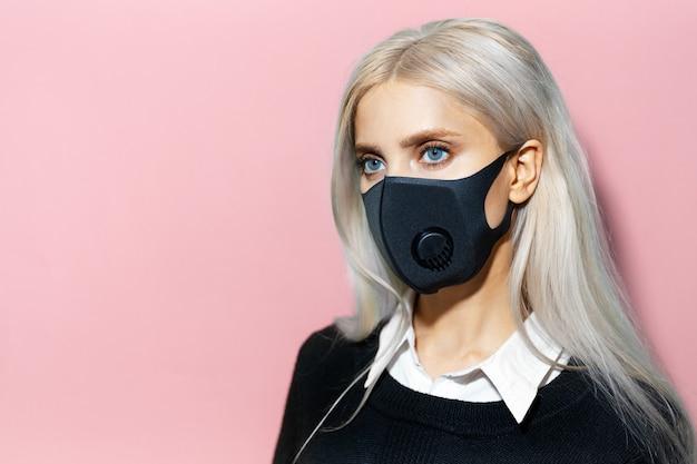 Giovane donna bionda che indossa una maschera facciale respiratoria contro i virus su sfondo rosa pastello con spazio per le copie.