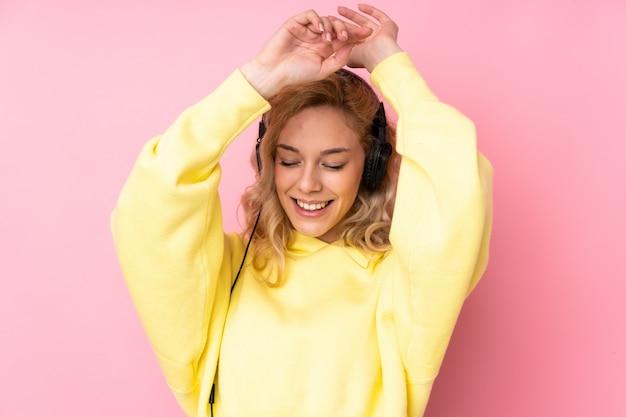 Giovane donna bionda che indossa una felpa isolata su musica e ballare d'ascolto della parete rosa Foto Premium