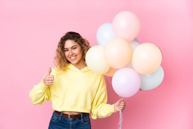 Giovane donna bionda con capelli ricci che cattura molti palloncini isolati su rosa dando un pollice in alto gesto
