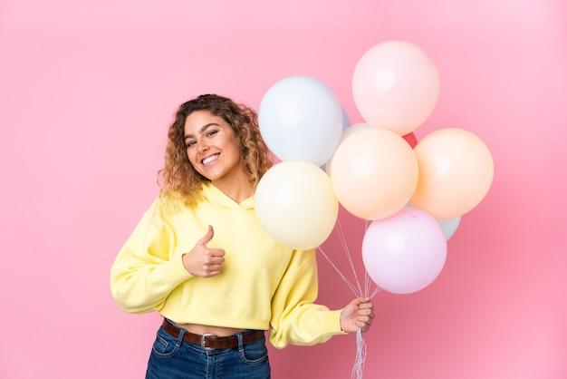 Giovane donna bionda con capelli ricci che cattura molti palloncini isolati sulla parete rosa dando un pollice in alto gesto
