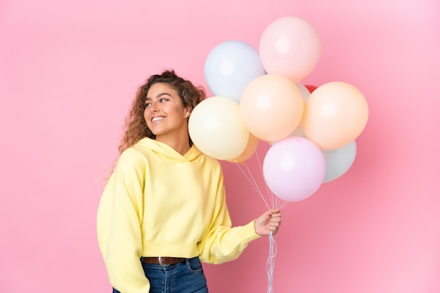 Giovane donna bionda con capelli ricci che cattura molti palloncini isolati sulla parete rosa