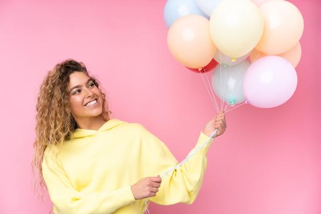 Giovane donna bionda con capelli ricci che cattura molti palloncini isolati in rosa