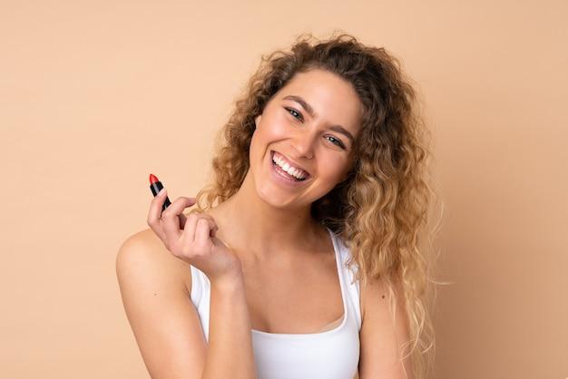 Giovane donna bionda con capelli ricci isolato su beige che tiene rossetto rosso