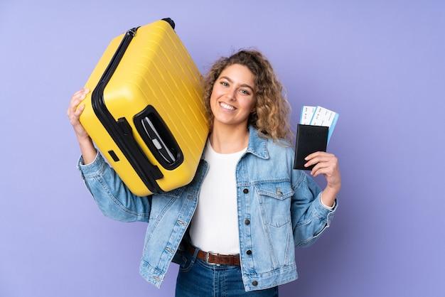 Giovane donna bionda con capelli ricci isolati su viola in vacanza con la valigia e il passaporto