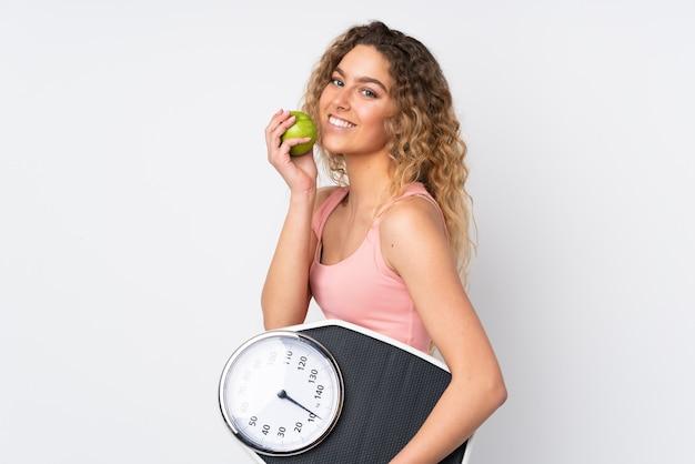Giovane donna bionda con capelli ricci isolato su bianco con pesatrice e con una mela