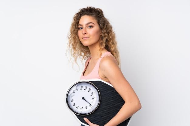 Giovane donna bionda con capelli ricci isolato su bianco con macchina di pesatura