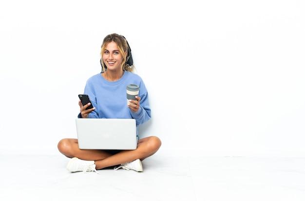 Giovane donna bionda con il computer portatile isolato tenendo il caffè da portare via e un cellulare