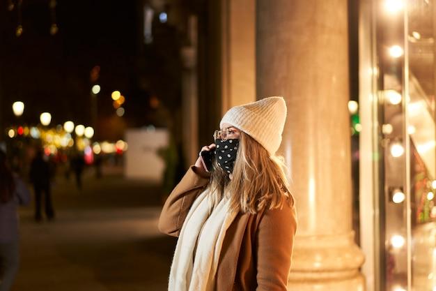 Giovane donna bionda con una maschera davanti alla vetrina di un negozio a parlare al telefono, in una città di notte, con luci sullo sfondo. atmosfera invernale.