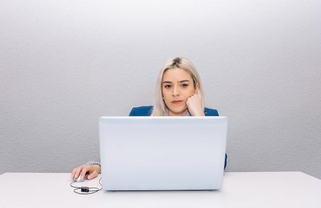 Giovane donna bionda con capelli platino vestita con un blazer blu telelavoro da casa con il laptop. concetto di telelavoro.