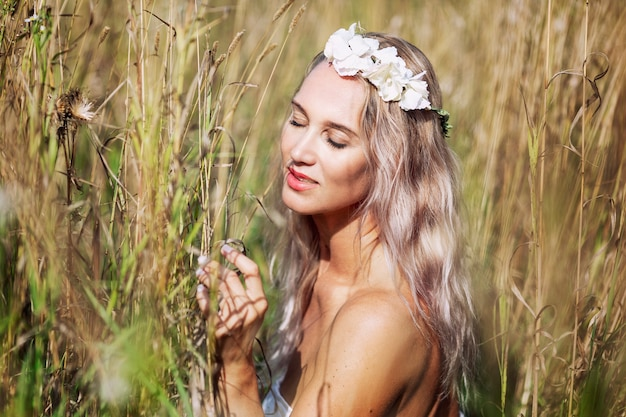 Giovane donna bionda con una corona bianca sulla sua testa in un campo per godersi la natura