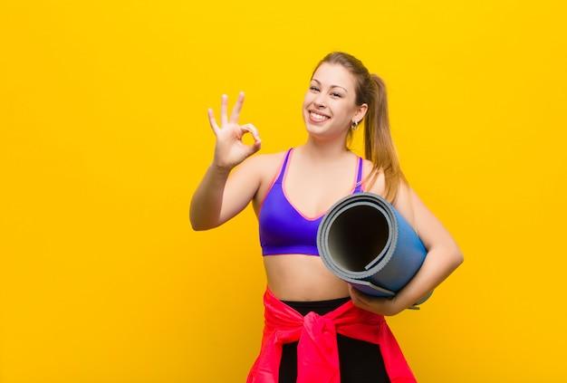 Giovane donna bionda con una stuoia di yoga. concetto di sport