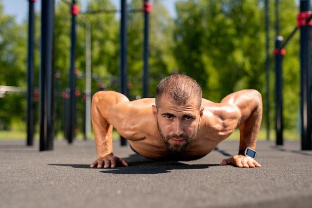 Giovane bodybuilder spingendo verso l'alto sopra il campo sportivo durante l'allenamento all'aperto