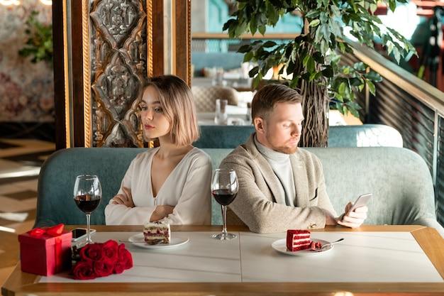 Giovane donna annoiata o offesa che si siede dalla tavola servita nel ristorante con il suo fidanzato che scorre nello smartphone nelle vicinanze