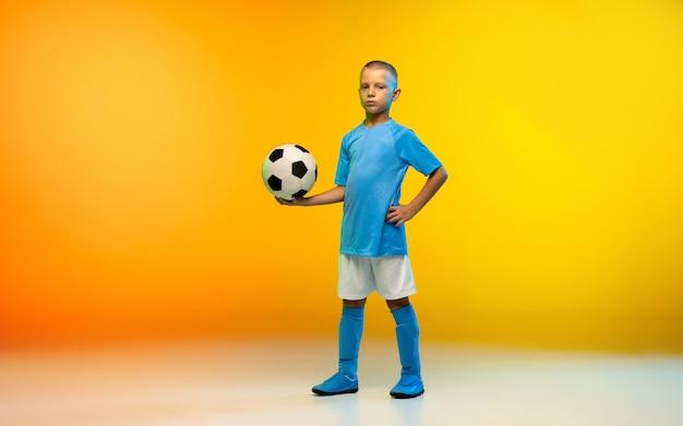 Giovane ragazzo come un giocatore di calcio o di calcio in abbigliamento sportivo che si esercita su una parete sfumata