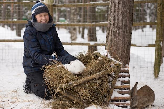 Un giovane ragazzo con un berretto blu che gioca con un coniglio bianco nel parco cittadino d'inverno