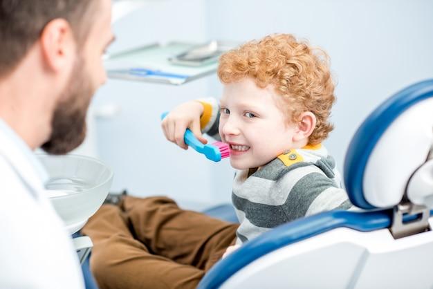 Ragazzo che si lava i denti con un grande spazzolino da denti seduto sulla sedia dello studio dentistico