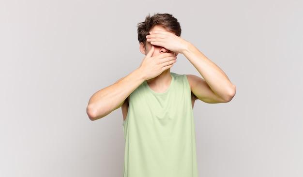 Ragazzo che copre il viso con entrambe le mani dicendo no alla telecamera! rifiutare le foto o vietare le foto