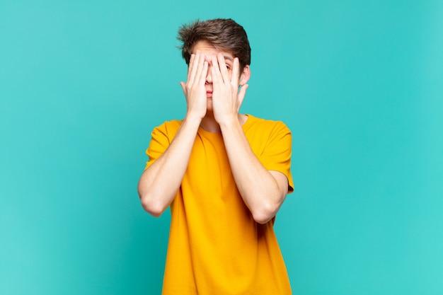 Ragazzo che copre il viso con le mani, sbirciando tra le dita con espressione sorpresa e guardando di lato