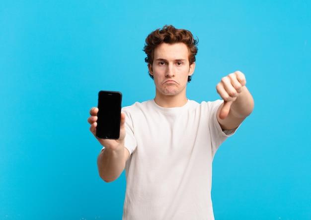Ragazzo che si sente arrabbiato, arrabbiato, infastidito, deluso o scontento, mostrando il pollice verso il basso con uno sguardo serio. concetto di schermo del telefono