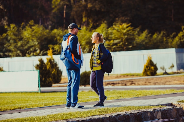 Ragazzo e ragazza prima dell'allenamento parlando allo stadio, preparandosi per l'allenamento