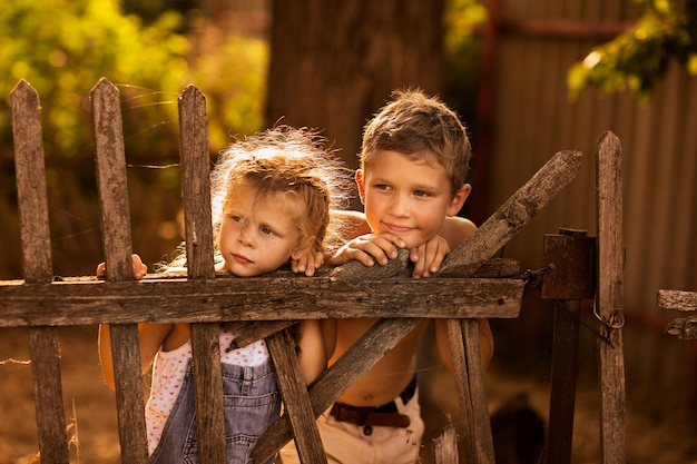 Il giovane ragazzo e ragazza con le trecce che giocano su un vecchio di legno recintano il paese. tramonto