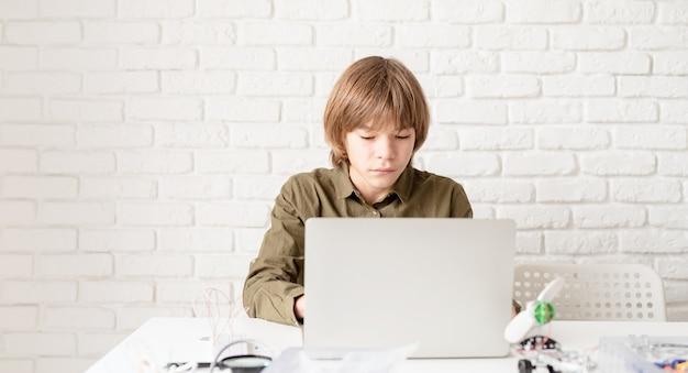 Giovane ragazzo in camicia verde che lavora o studia sul computer portatile a casa