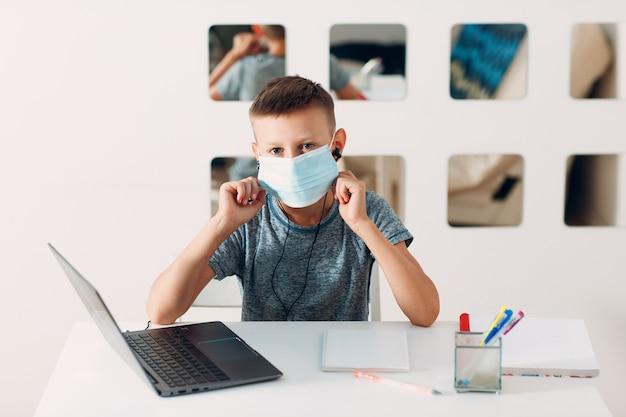 Giovane ragazzo in cuffia seduto al tavolo con laptop e maschera medica e si prepara a scuola
