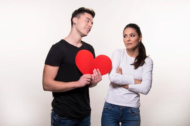 Giovane ragazzo che tiene un cuore rosso e la ragazza sta dubitando isolato su sfondo bianco