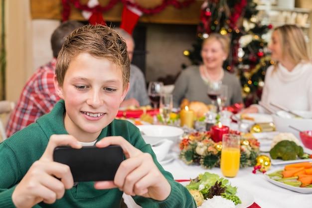 Giovane smartphone della tenuta del ragazzo durante la cena di natale