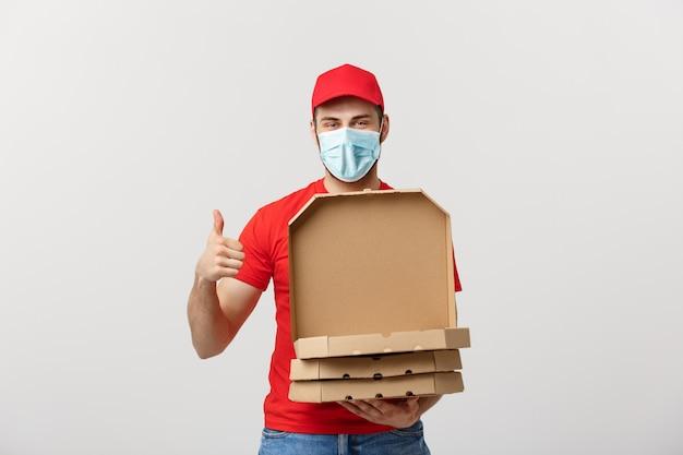 Il giovane ragazzo sta consegnando e mostrando scatole per pizza in scatole.