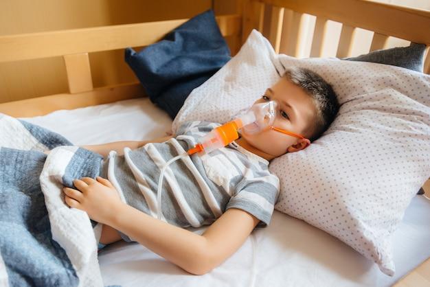 Un ragazzo riceve un'inalazione durante una malattia polmonare. medicina e cura