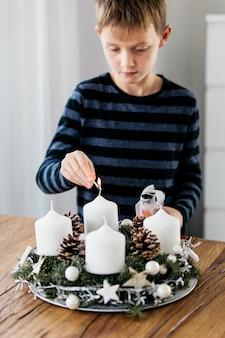 Ragazzo giovane accendendo la prima candela sulla corona dell'avvento contando quattro settimane fino al natale tradizione svizzera