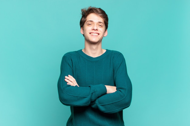 Ragazzo che sembra un uomo d'azione felice, orgoglioso e soddisfatto che sorride con le braccia incrociate