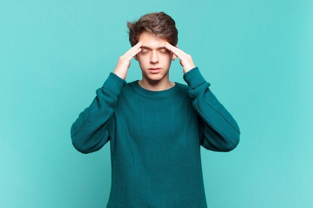 Ragazzo che sembra stressato e frustrato, lavora sotto pressione con mal di testa e turbato da problemi