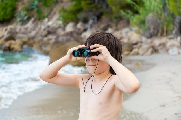 Un giovane ragazzo che guarda attraverso il binocolo che soggiornano in riva al mare sulla spiaggia.
