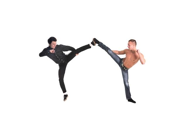 Un giovane ragazzo e un uomo hanno ritratto il karate isolato su sfondo bianco