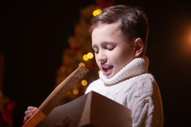 Giovane ragazzo che apre un regalo di notte