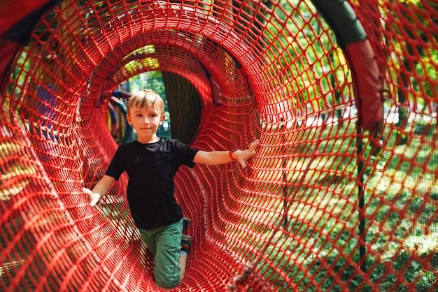 Giovane ragazzo che passa il tunnel del cavo. infanzia felice. vacanze estive. il ragazzo sveglio si arrampica su una rete rampicante della corda. parco avventura a fune.