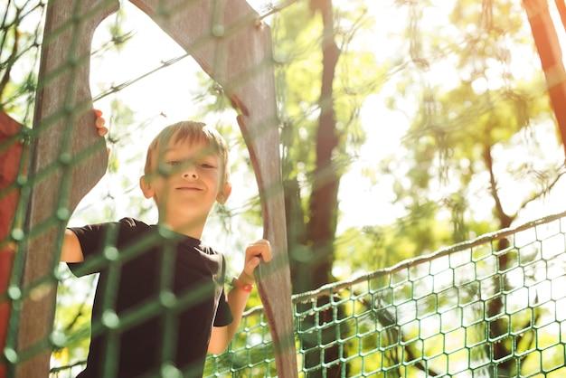 Giovane ragazzo che passa il tunnel del cavo. parco giochi all'aperto, tempo libero per bambini. infanzia felice.