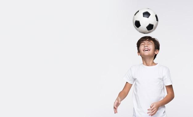 Giovane ragazzo che gioca con la sfera di calcio