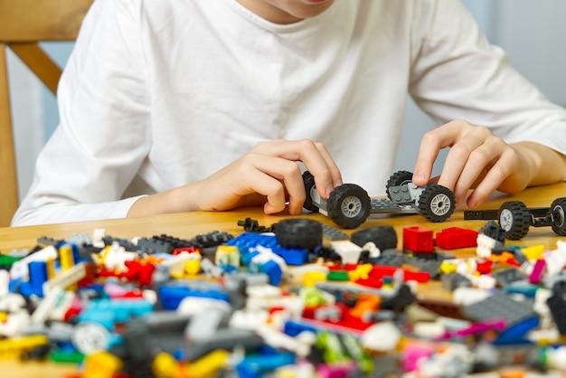 Giovane ragazzo che gioca con i giocattoli di costruzione in plastica a casa.