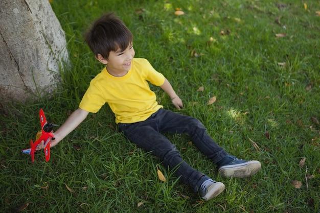Giovane ragazzo che gioca con un aereo giocattolo al parco