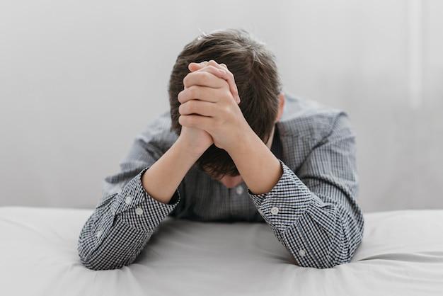 Giovane ragazzo che prega con la sua testa in giù