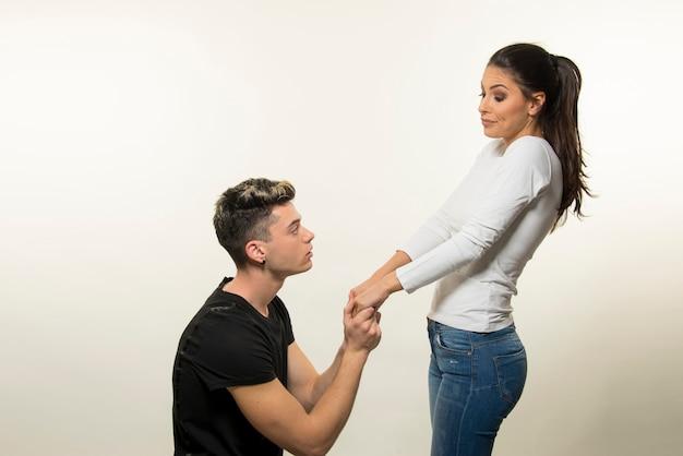 Giovane ragazzo che propone alla ragazza su sfondo bianco