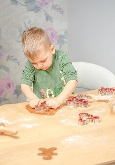 Un giovane ragazzo spinge le forme di pan di zenzero. prepararsi per il natale.
