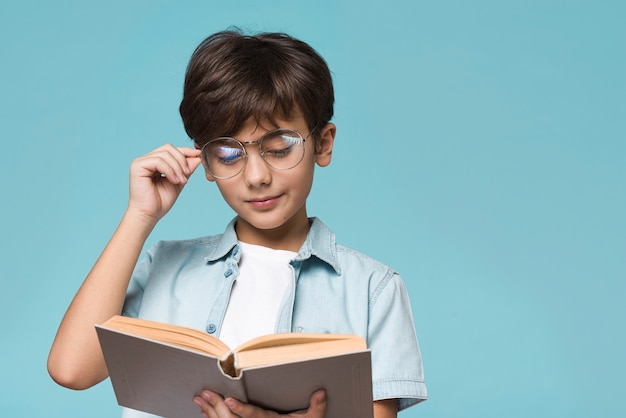 Giovane lettura del ragazzo con copia-spazio