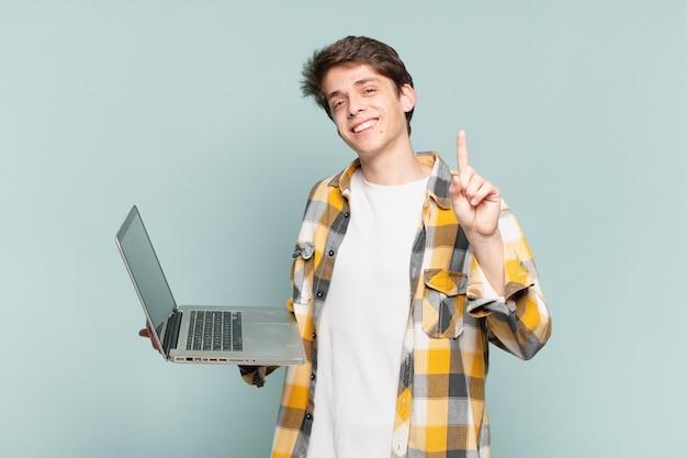 Giovane ragazzo sorridente e dall'aspetto amichevole, mostrando il numero uno o il primo con la mano in avanti, conto alla rovescia. concetto di laptop